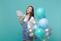 Pensive woman looking up hold fan of money in dollar banknotes cash money celebrating with colorful air balloons