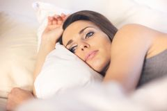 Pensive Woman Lying on Bed Stock Images