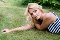 Pensive woman lying on grass. Royalty Free Stock Image