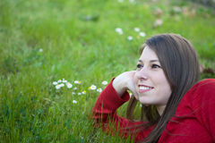 Pensive woman lying in the grass with lots of flowers Royalty Free Stock Images