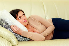 Pensive woman lying on the sofa Stock Images