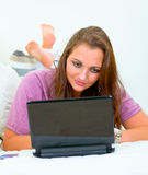 Pensive woman lying on sofa and using laptop Stock Images
