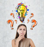 Pensive woman, orange questions and bulb Royalty Free Stock Photography