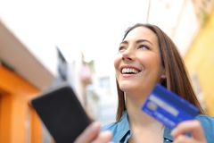 Pensive woman pays online with credit card in the street royalty free stock photography