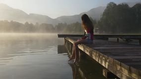 Pensive woman on pier of mountain lake. In sunrise fog over the water stock video
