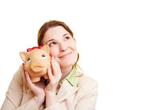 Pensive woman with piggy bank Stock Photo
