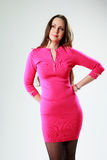 Pensive woman in pink dress standing Stock Images