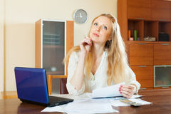 Pensive  woman reading  documents at home Royalty Free Stock Photos