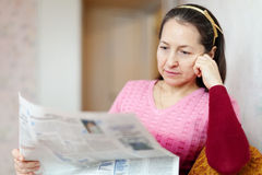 Pensive woman reading newspaper Royalty Free Stock Photo