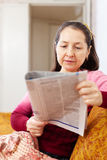 Pensive woman reading newspaper Stock Images