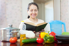 Pensive  woman reads cookbook for recipe Royalty Free Stock Images