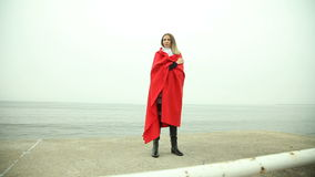 Pensive woman in red blanket on the sea shore Stock Photography