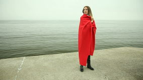 Pensive woman in red blanket on the sea shore Royalty Free Stock Images