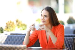 Pensive woman relaxing drinking coffee in a bar terrace. Pensive woman relaxing drinking coffee looking away sitting in a bar terrace stock images