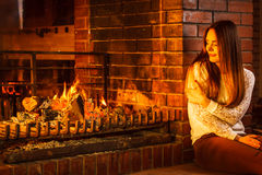 Pensive woman relaxing at fireplace. Winter home. Stock Photo