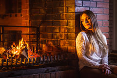 Pensive woman relaxing at fireplace. Winter home. Royalty Free Stock Images
