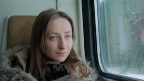 Pensive woman relaxing and looking out of a train window. Close up shot of pensive woman relaxing and looking out of a train window. Travel, transport and winter stock video footage