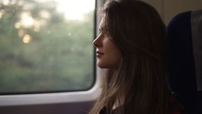 Pensive woman relaxing and looking out of a train window. Side view. Travel, transport concept