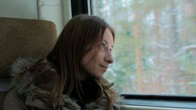 Pensive woman relaxing and looking out of a train window stock video