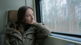 Pensive woman relaxing and looking out of a train window stock footage