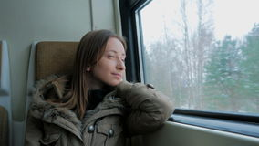 Pensive woman relaxing and looking out of a train window. Travel, transport and winter concept stock video