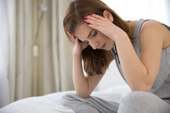 Pensive woman sitting on the bed Royalty Free Stock Images