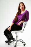 Pensive woman sitting on the chair. Over gray background Stock Images