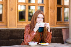 Pensive woman sitting with coffee cup and dreaming outdoors Royalty Free Stock Image