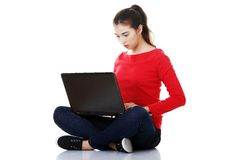 Pensive woman sitting cross-legged with laptop Stock Photography