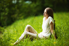 Pensive woman sitting on the grass Stock Image