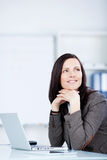 Pensive woman sitting at her desk Royalty Free Stock Photos