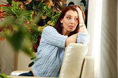 Pensive woman sitting on the sofa Royalty Free Stock Photography