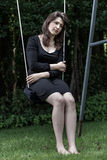 Pensive woman sitting on the swing Stock Photography