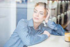 Pensive woman sitting and thinking in cafe Stock Images