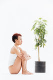 Pensive woman sitting and thinking near small tree in pot Royalty Free Stock Photos