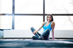 Pensive woman sitting on yoga mat Royalty Free Stock Images