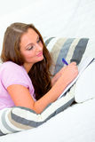 Pensive woman on sofa and writing in notebook Royalty Free Stock Image
