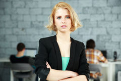 Pensive woman standing with arms folded Royalty Free Stock Photos