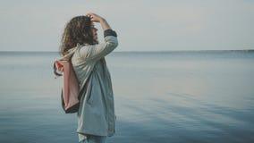 The pensive woman standing near the sea stock photos