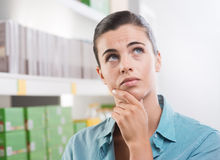 Pensive woman at store. Pensive young woman at store looking up with supermarket shelves on background Stock Image