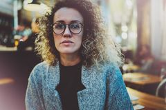 Pensive woman in stylish clothing wearing eye glasses outside in the european night city. Bokeh and flares effect on. Blurred background royalty free stock photos