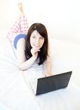 Pensive woman surfing the internet lying on a bed Royalty Free Stock Photos