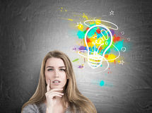 Pensive woman in sweater and light bulb Stock Photography