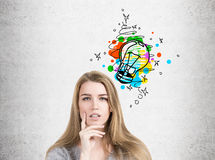 Pensive woman in sweater and light bulb, concrete Stock Photos