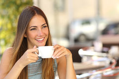 Pensive woman thinking in a coffee shop terrace stock images