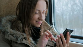Pensive woman traveling on a train and using a smartphone. Close up shot. Pensive woman traveling on a train and using a smartphone. Travel, transport and stock footage