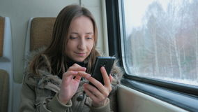 Pensive woman traveling on a train and using a smartphone. Travel, transport and technology concept stock video footage