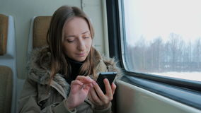 Pensive woman traveling on a train and using a smartphone. Travel, transport and technology concept stock video