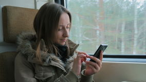 Pensive woman traveling on a train and using a smartphone stock footage