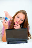 Pensive woman using credit card for net shopping Royalty Free Stock Photo